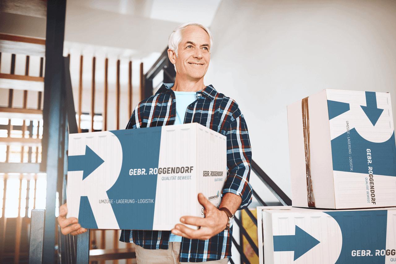 Älterer Mann mit Umzugskartons während Seniorenumzug